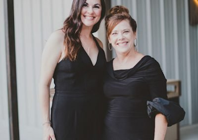 Two women posing for a photo in formal attire.