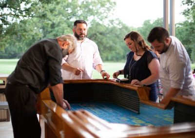 Three individuals playing craps at a casino event.